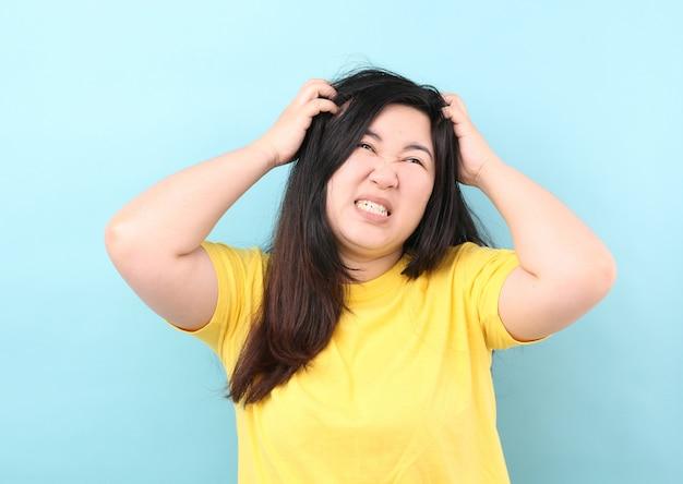 Le donne dell'asia del ritratto sentono il prurito dei capelli, su un fondo blu in studio.