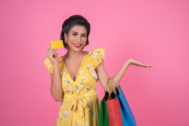 Le donne della moda amano fare shopping con la borsa della spesa e la carta di credito