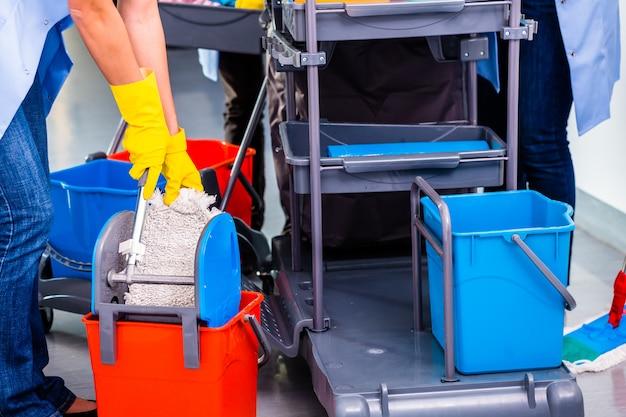 Le donne delle pulizie lavavano il pavimento