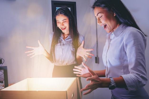 Le donne di affari che aprono la scatola di cartone con l'emozione sorpresa per qualcosa di miracolo all'interno.