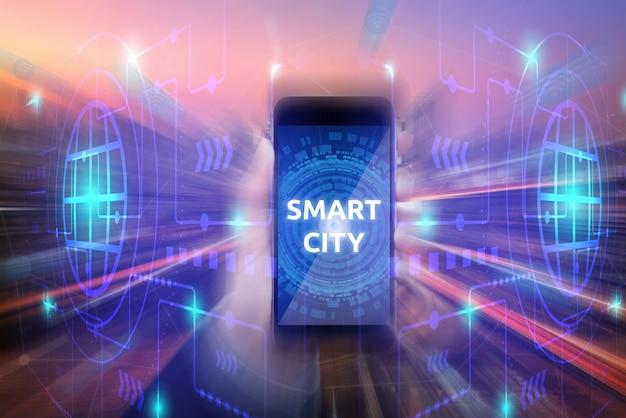 Le donne di affari mostrano uno smartphone con la città astuta sullo schermo su fondo di tecnologia.