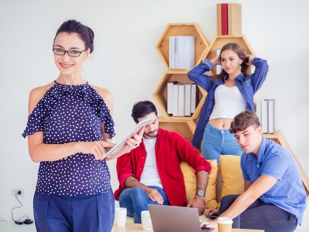 Le donne di affari stanno e posano sul lavoro