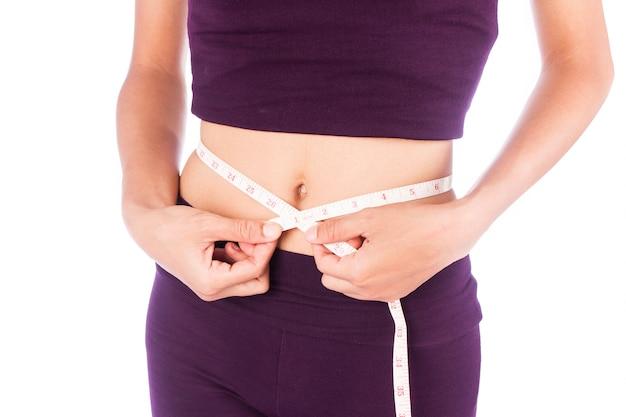 Le donne di bellezza vita sottile con un metro misurano la sua forma