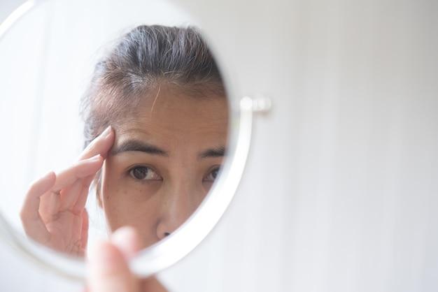 Le donne di mezza età guardano allo specchio per vedere le rughe del viso.