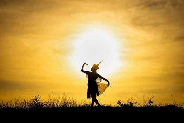 Le donne di silhouette manohra ballano con il tramonto nel sud della thailandia.