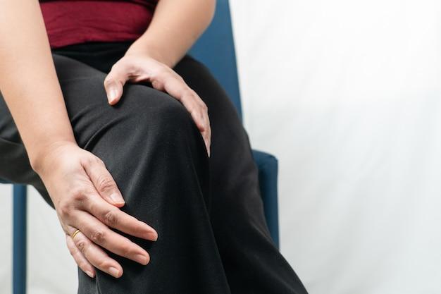 Le donne doloranti al ginocchio, le donne toccano il dolore al ginocchio a casa