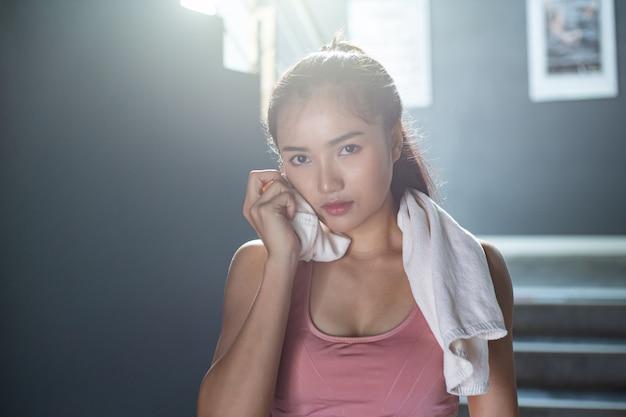 Le donne dopo l'allenamento, pulire il viso con un panno bianco in palestra.