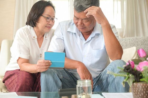 Le donne e gli uomini asiatici anziani si siedono sul sofà, fanno i piani finanziari.
