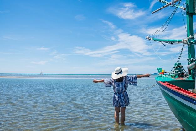 Le donne e i grandi cappelli viaggiano fino al mare in estate.
