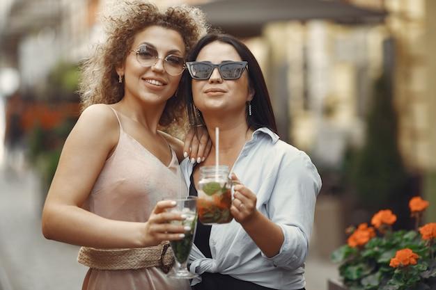 Le donne eleganti bevono cocktail in una città estiva