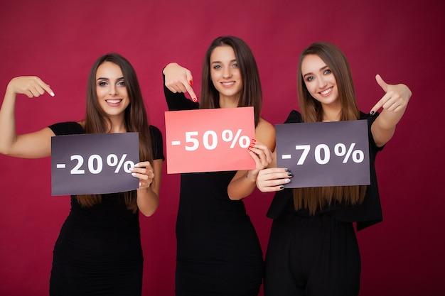Le donne eleganti del brunette indossa i sacchetti della spesa neri della tenuta del vestito, concetto nero di venerdì
