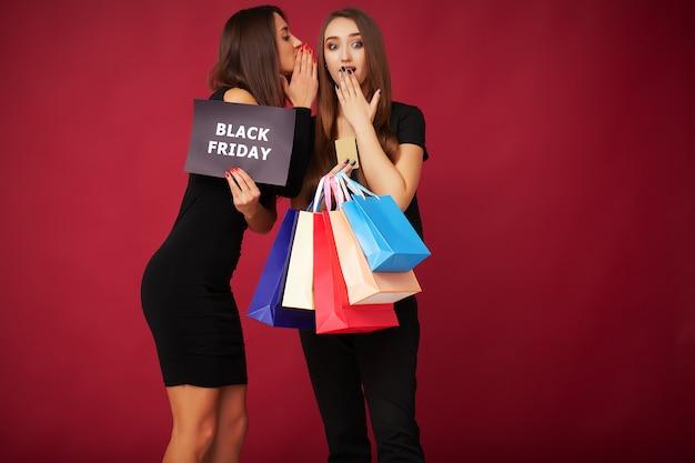 Le donne eleganti del brunette indossa i sacchetti della spesa neri della tenuta del vestito, concetto nero di venerdì.