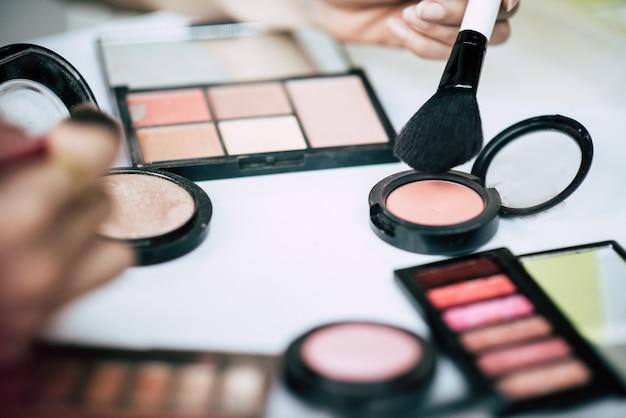 Le donne facendo il trucco con pennello e cosmetici