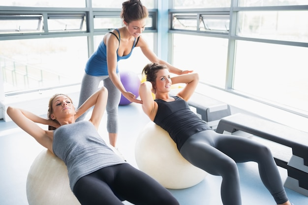Le donne facendo sit-up sulle palle di esercizio in palestra