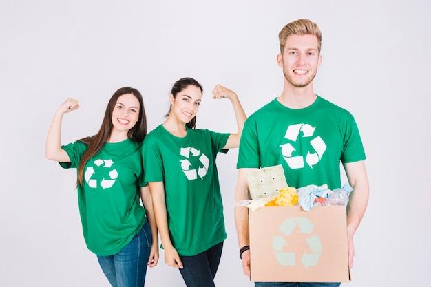 Le donne felici che flettono i loro muscoli dietro la tenuta dell'uomo ricicla la scatola di cartone degli oggetti