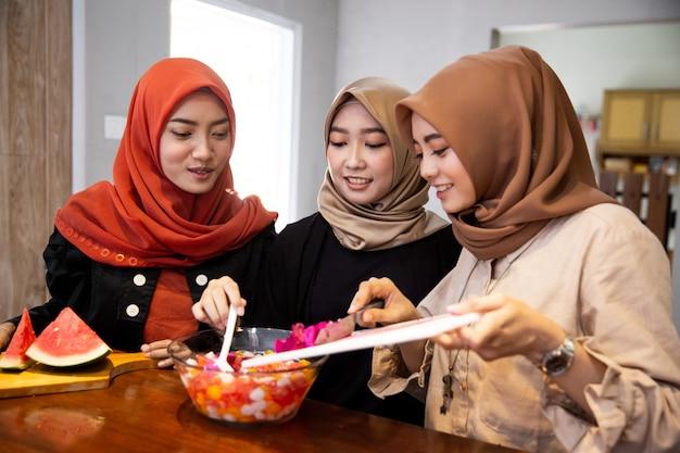 Le donne hijab preparano cocktail di bevande fresche