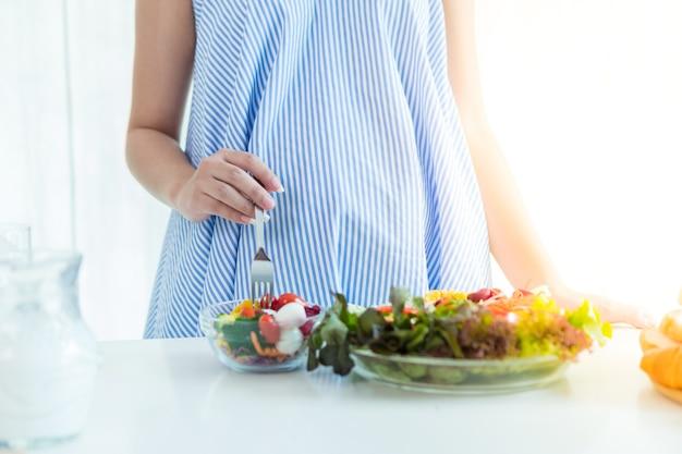 Le donne incinte indossano un abito blu. prendi latte e insalata sul tavolo.