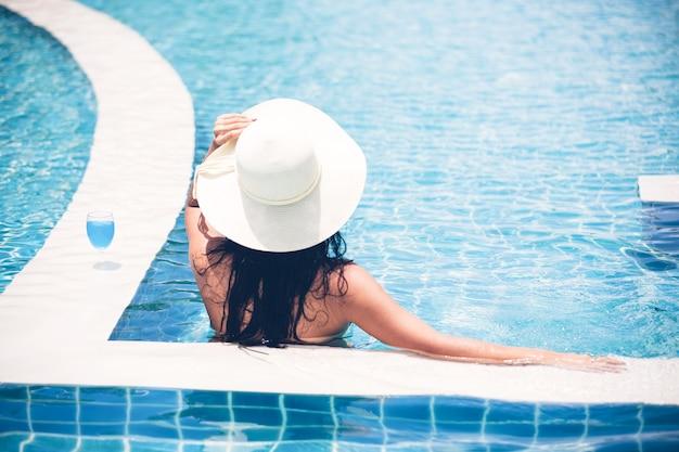 Le donne indossano bikini e bevono cocktail nella calda estate in piscina