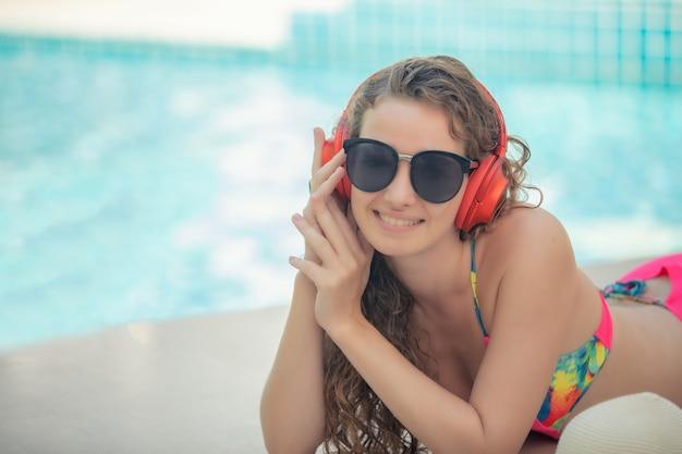 Le donne indossano bikini, leggono libri e ascoltano musica nella piscina estiva.