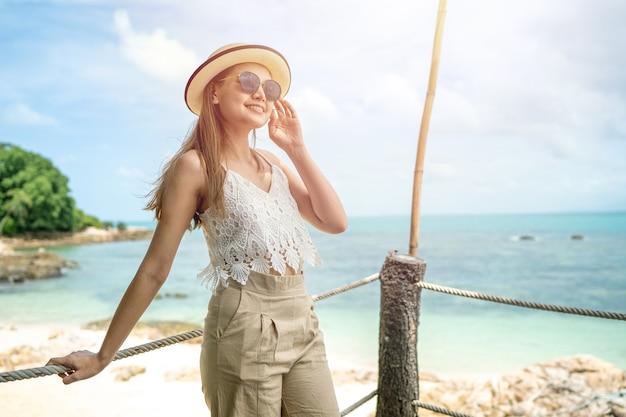 Le donne indossano un cappello da mare che è felice e stanno sul ponte di legno e guardano al mare sulla spiaggia