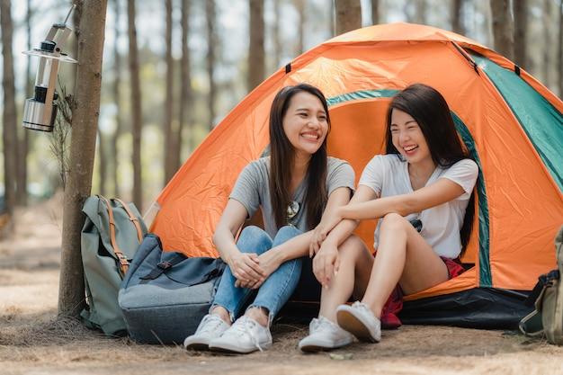 Le donne lesbiche di lgbtq coppia il campeggio o fanno un picnic insieme nella foresta