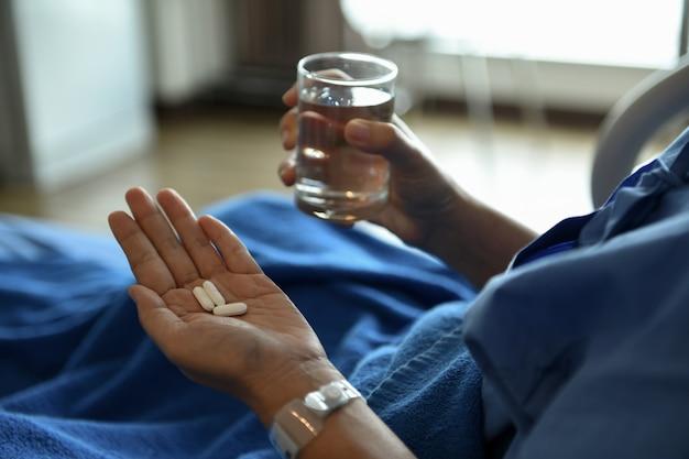 Le donne malate si siedono su un letto. ha medicine e un bicchiere d'acqua in mano.