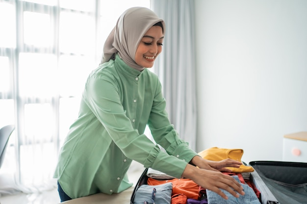 Le donne musulmane che indossano l'hijab preparano i vestiti da mettere in una valigia