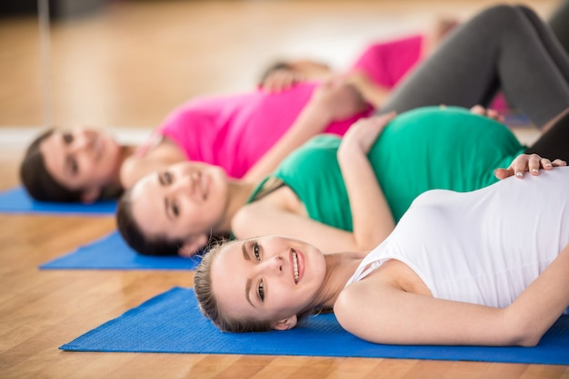 Le donne nella classe di yoga sono distese su tappetini in una palestra.