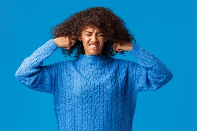 Le donne odiano le canzoni di natale suonano ovunque. donna afroamericana dispiaciuta e infastidita