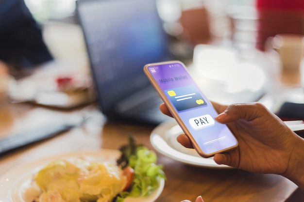 Le donne pagano per il cibo usando le carte di credito tramite telefoni cellulari nei ristoranti, futuri iot e concetti tecnologici