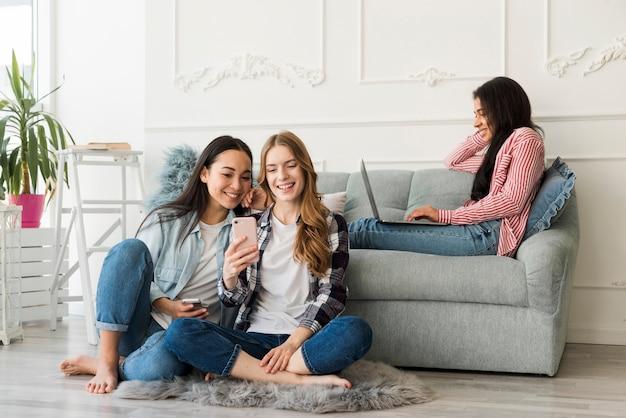 Le donne passano il tempo insieme a lavorare sul portatile