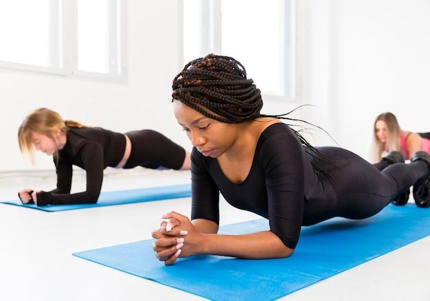 Le donne praticano l'esercizio di resistenza sul tappetino