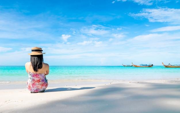 Le donne sedute sulla spiaggia e sul mare hanno una vacanza estiva all'insegna del relax