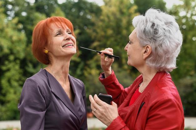 Le donne senior con compongono all'aperto