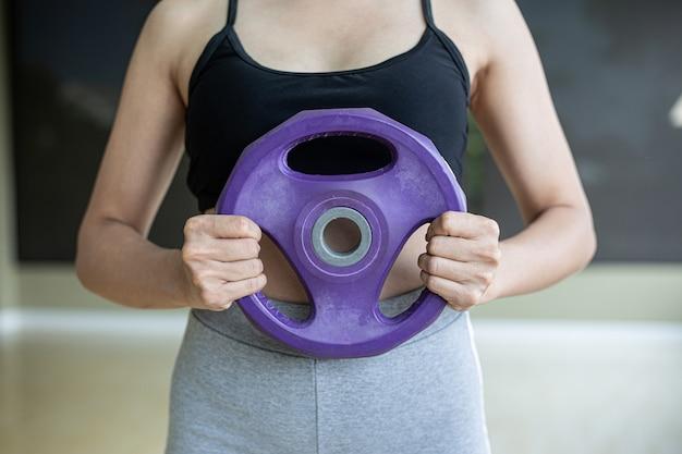 Le donne si esercitano con manubri pesi sul petto.
