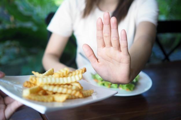 Le donne si rifiutano di mangiare fritti o patatine fritte per perdita di peso e buona salute.