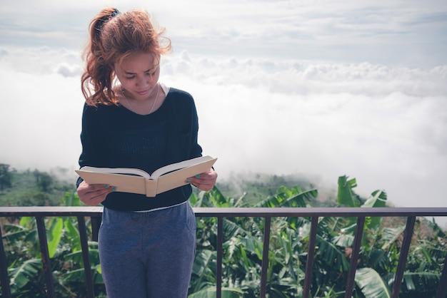 Le donne si rilassano leggi il libro del mattino bel tempo cielo nebbia. in montagna, l'atmosfera del mattino.