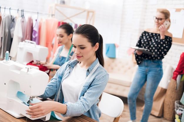 Le donne sono sedute dietro le macchine da cucire.