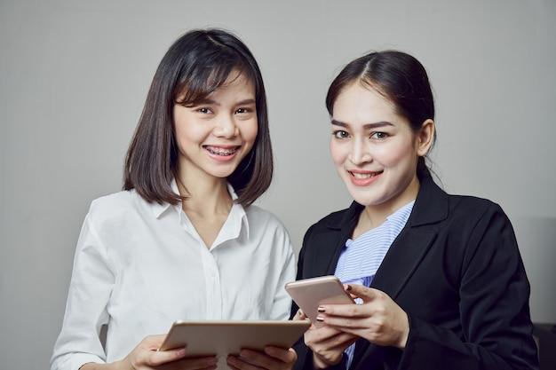 Le donne sorridenti di affari stanno tenendo la compressa e stanno usando le applicazioni online.