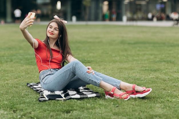 Le donne sorridono utilizzano lo smartphone del selfie dello scatto del cellulare dello smart phone in parco