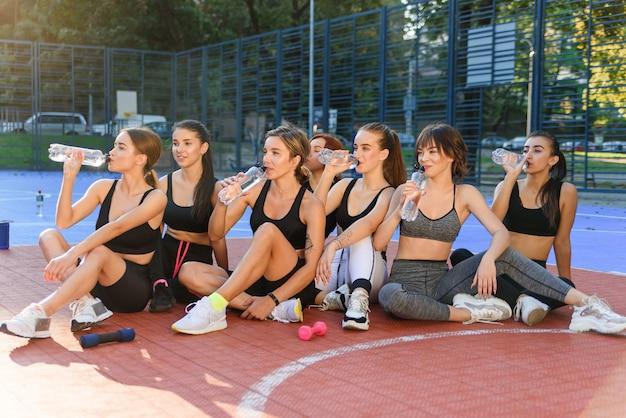 Le donne sportive allegre in abiti sportivi che riposano dopo l'allenamento cardio fitness intenso e bevono l'acqua dalla bottiglia sul campo sportivo all'aperto.