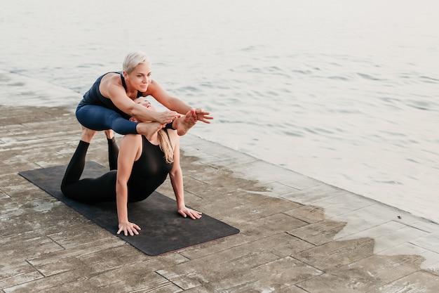 Le donne sportive che fanno l'acro yoga si esercitano vicino al mare sulla spiaggia