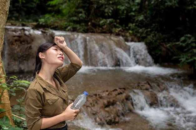 Le donne stanno facendo un'escursione bevendo acqua fresca nella foresta