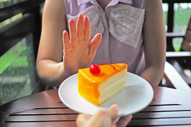 Le donne stanno perdendo peso. scegli di non avere un piatto di torta che gli amici mandano.