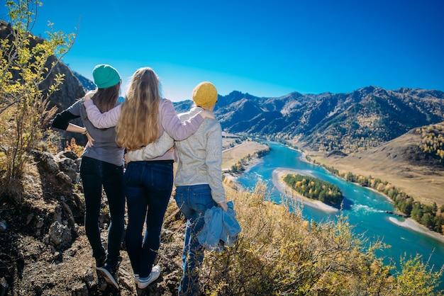 Le donne stanno su una collina e guardano un fiume di montagna