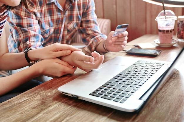 Le donne tengono caldo l'uomo della mano che compera online con la carta di credito e il computer portatile, prestito della famiglia