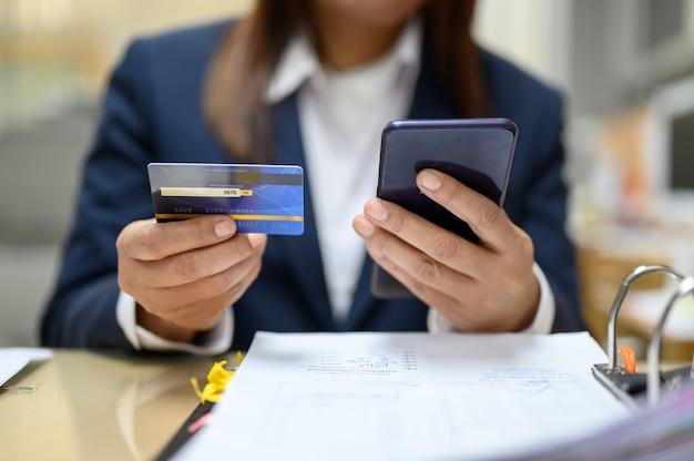 Le donne tengono carte di credito e telefoni cellulari per ordinare prodotti online.