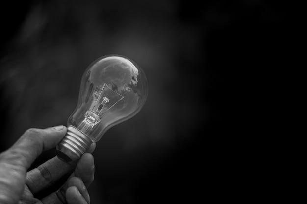 Le donne tengono la lampadina al buio. - nuova idea e concetto di innovazione.