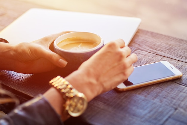 Le donne tengono smartphone durante la pausa caffè in un caffè