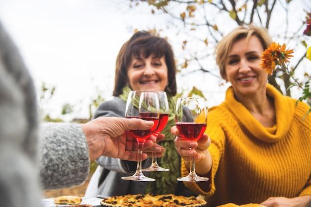 Le donne tintinnano di bicchieri di vino alla cena di famiglia in autunno.